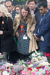 Parliament Square, Westminster, London, June 17th 2016. Following the murder of Jo Cox MP a vigil is held as friends and members of the public lay flowers, light candles and leave notes of condolence and love in Parliament Square, opposite the House of Commons. PICTURED: A grief-stricken woman wearing a Jo Cox rosette sobs as she views the tributes.