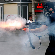 A Turkish riot policeman fires tear gas during clashes with police on Istiklal Avenue in Istanbul, Turkey, on July 6, 2013. Photo by AYKUT AKICI/TURKPIX