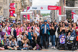 Large crowd watch street performance on High Street during Edinburgh Fringe Festival 2016 in Scotland , United Kingdom