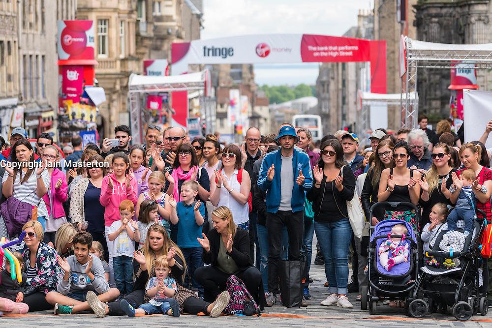 Large crowd watch street performance on High Street during Edinburgh Fringe Festival 2016 in Scotland , United Kingdom