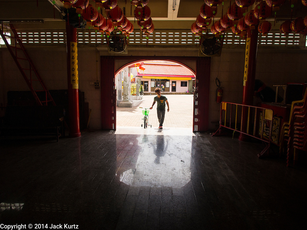27 DECEMBER 2014 - PHUKET TOWN, PHUKET, THAILAND: A man walks a bicycle into Pud Jor Shrine, a large Chinese shrine in Phuket town. The bike will be given to a needy child on Thai Children's Day, which is January 10 in 2015. Phuket has a large Chinese minority that is active in business and civic life.    PHOTO BY JACK KURTZ