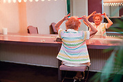 Elderly woman fixing her hair in the mirror of a dressing room