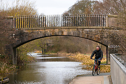 Edinburgh, Scotland, UK. 25 March, 2020. Day two of the Government enforced lockdown in the UK. All shops and restaurants and most workplaces remain closed. Cities are very quiet with vast majority of population staying indoors. Pictured; A cyclist taking daily exercise alongside the Union Canal at Hermiston in Edinburgh. Iain Masterton/Alamy Live News