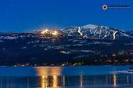 Lights from night skiing at Whitefish Mountain Resort reflect at Whitefish Lake State Park, Montana, USA