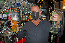 ©Licensed to London News Pictures 03/07/2020     <br /> Chislehurst, UK. Landlord Alan Weeks holding a beer and sanitiser spray, he will be serving punters wearing surgical gloves and wearing a mask. The Imperial Arms pub and courtyard bistro in Chislehurst, South East London is preparing to open its doors again after three months of coronavirus lockdown.  Photo credit: Grant Falvey/LNP