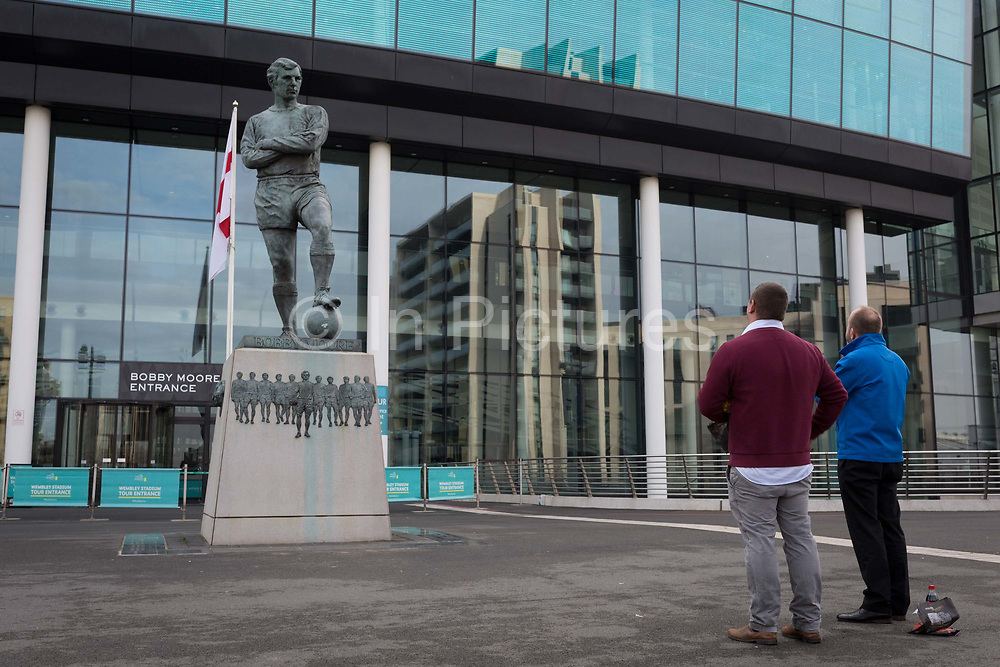 Two football fans pay their respects to the statue of English footballs most loved player, Bobby Moore, on 6th November 2019, in Wembley, London, England. Sir Bobby Moore captained England to its World Cup victory against Germany at the old Wembley stadium in 1966.
