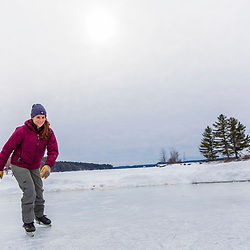 A woman ice skating on Long Lake in Harrison, Maine.