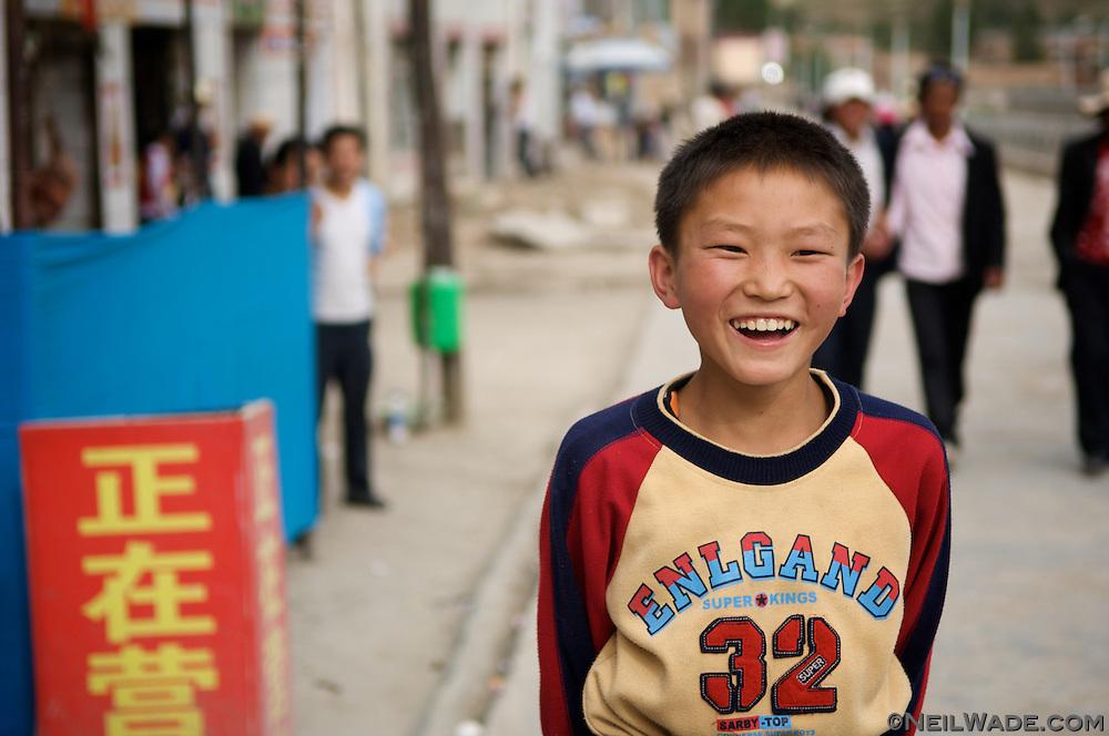 Ayoung Tibetan boy laughs as his picture is taken in Yushu, Tibet.