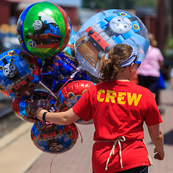 Strasburg, PA, USA - June 20, 2017: A crew member takes Thomas the Tank Engine balloons toward the train station in Strasburg, Lancaster County.