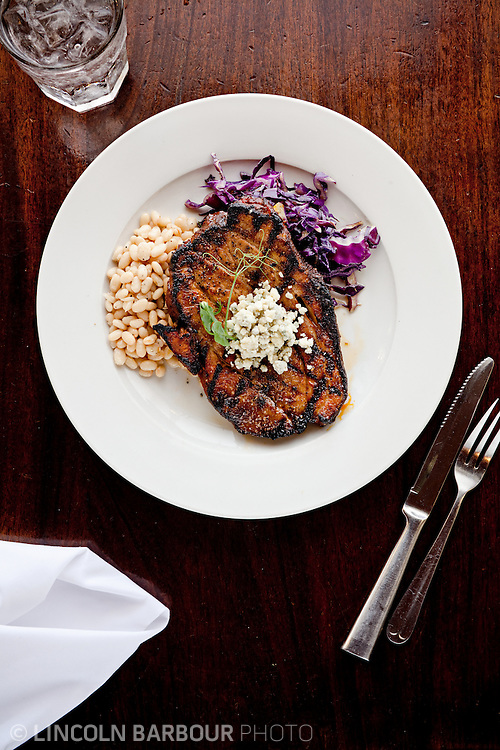 A top down view of a steak with excellent grill marks and topped with blue cheese. On the plate are some beans and sauteed red cabbage.