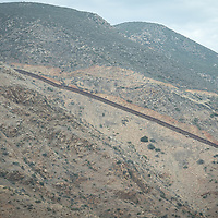 The US/Mexico border wall near Mexicalli, northern Mexico. Thousands of migrants pass over the wall in this region each year, and many go through the desert to reach the US, large numbers of them die along the way, of heatstroke or dehydration.