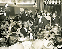 1953 Vic Damone shakes hands with Humphrey Bogart. Jack Benny and Jane Wyman behind Damone. Lauren Bacall seated at right. Mary Livingstone pulling Damone's coat.