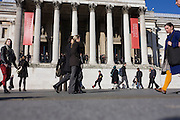 Tourists and other pedestrians walk past a street juggling busker in Trafalgar Square, Westminster, central London.