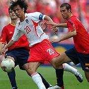 Republic of Korea's Myung Bo Hong gets past Spain's Ivan Helguera