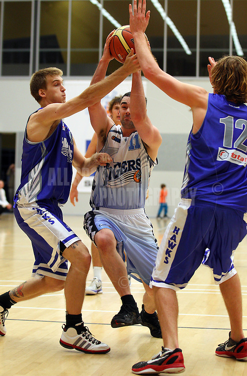 PERTH, AUSTRALIA - JULY 16: Alex Prince of the Tigers drives to the basket against Rory Pekin and Joshua Garlepp of the Hawks during the week 18 SBL game between the Perry Lakes Hawks and the Willetton TIgers at The State Basketball Center on July 16, 2011 in Perth, Australia.  (Photo by Paul Kane/Allsports Photography)