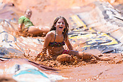 A young girl slips down a mud slide during the 2015 National Red Neck Championships May 2, 2015 in Augusta, Georgia. Hundreds of people joined in a day of country sport and activities.