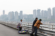 A man selling trinkets walk down a path overlooking the Jialing River in Chongqing, China, on Tuesday, April 12, 2016. The municipality of 30 million people saw state-led development approach fueled the fastest pace nationwide, with President Xi Jinping praising policy innovations that have included subsidized housing and relaxed residency rules that encourage labor mobility.
