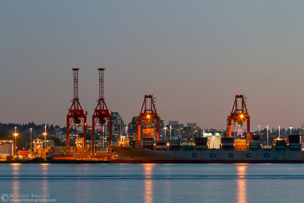 Shipping containers are offloaded from a cargo ship at the Port of Vancouver by these large cranes.  Photographed from across Burrard Inlet at North Vancouver, British Columbia, Canada.