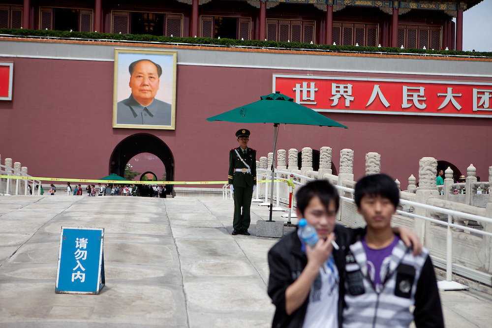 """Visitors and tourists getting photographed in front of the famous Mao portrait at the main gate of """"The Forbidden City"""" which was the Chinese imperial palace from the Ming Dynasty to the end of the Qing Dynasty. It is located in the middle of Beijing, China. Beijing is the capital of the People's Republic of China and one of the most populous cities in the world with a population of 19,612,368 as of 2010."""