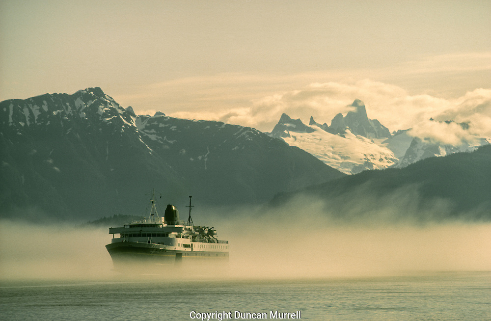 I took this photo from the end of the salmon cannery where I worked from 1979-86. The Devils Thumb mountain is clearly visible on the border between Canada and the USA.This photo was my first photo to be used by the Alaskan Marine Highway, and appeared on the cover of the ferry schedule. They used several more of my photos in exchange for free passes every year.