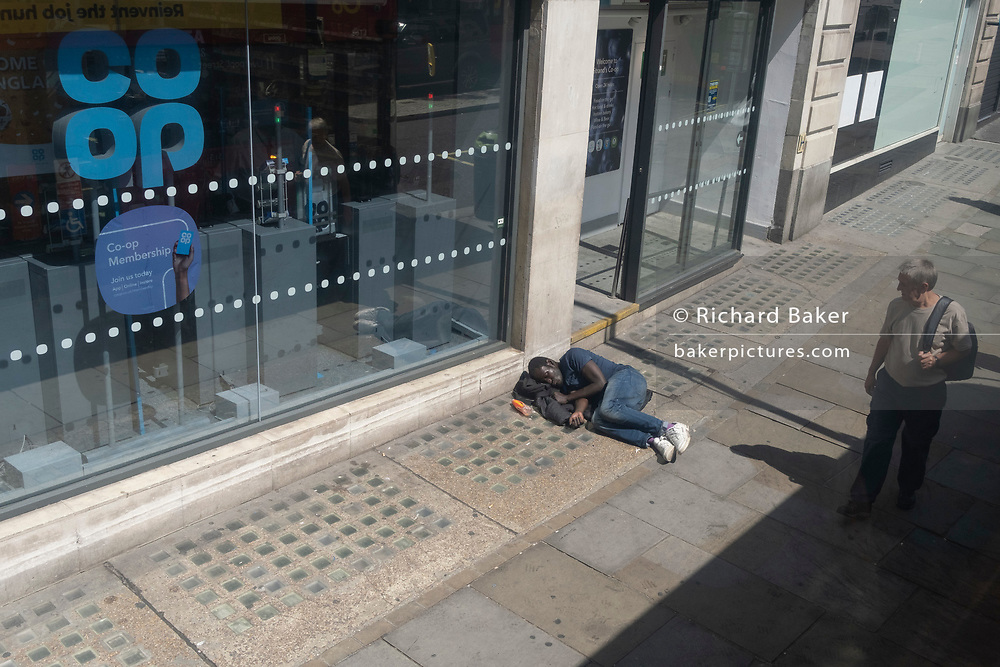 A wealthier man looks down at a black male lying on the pavement outside a branch of the Co-Op bank on the Strand, on 23rd June 2021, in Westminster, London, England.