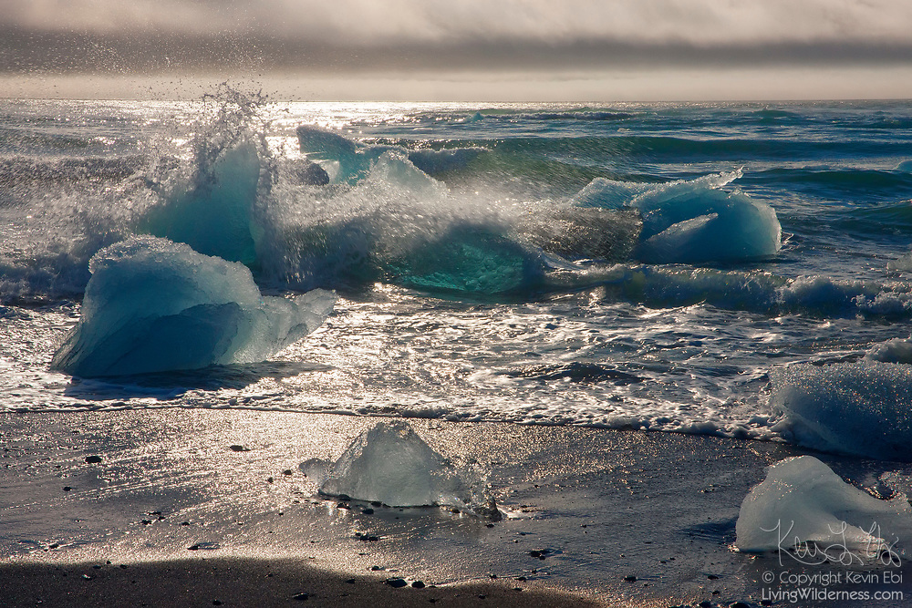 Atlantic Ocean waves crash into icebergs that have washed ashore at Breiðamerkursandur, a beach in southeast Iceland.