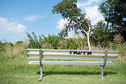 """A bench with """"Truth"""" spray painted on the back sits on football field at the Prime Prep Academy campus in Dallas, Texas on August 5, 2014. (Cooper Neill for The New York Times)"""