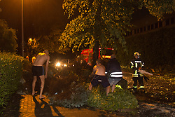 © Licensed to London News Pictures. 09/06/2014. Mülheim an der Ruhr, Germany. Neighbours help the fire brigade clear up debris. After a very hot day with temperatures reaching the mid 30 degrees centigrate, severe thunderstorms cause havoc in the Ruhr Area in Mülheim an der Ruhr and surrounding towns in North Rhine-Westphalia, Germany. Photo credit: Bettina Strenske/LNP