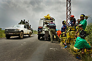 Victims of sexual violence at right, some of them also gave a birth to babies from the rapes, stand alongside the road to Kichanga, as a pick-up truck of government soldiers drives by.