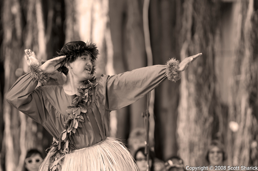 A young male dances the hula with outstretched arms in these pictures from Hawaii.