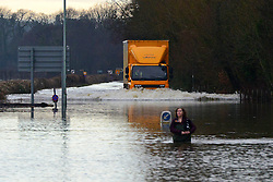 © Licensed to London News Pictures. 10/02/2014. Old Windsor, UK. A woman wading through the floodwater gets caught in the wash from a lorry traveling through the water.  Flooding in OLD WINDSOR in Berkshire today 10th February 2014 after the River Thames burst its banks. The Environment Agency has issued 14 Severe Flood Warnings alone the Thames. Photo credit : Stephen Simpson/LNP