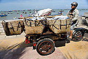 Modified three-wheel motorcycle (aka motorcyclo) loaded up with baskets full of fresh fish and ice. Bai Truoc (Front Beach, aka Tam Duong beach or Hang Dua bay), Vung Tau, Vietnam