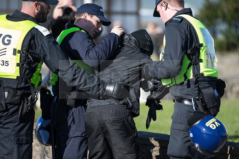 © Licensed to London News Pictures . 22/10/2016 . Margate , UK . An anti fascist protester is detained by police . A White Lives Matter protest and march , opposed by antifascists , is held in Margate , Kent . Photo credit : Joel Goodman/LNP