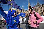 Anti Brexit protester with a blue wig and yellow heart shaped sunglasses tries on some cat ear headphones from a passing woman in Westminster as the Prime Minister arrives in Brussels to request an extension to Article 50 so the UK can continue to try to agree a Brexit Withdrawal Agreement on 10th April 2019 in London, England, United Kingdom. With just two days until the UK is supposed to be leaving the European Union, the delay decision awaits.