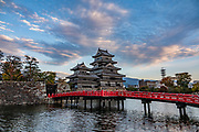 "At dusk, Matsumoto Castle can best be admired by its red bridge. The castle was built from 1592-1614 in Matsumoto, Nagano Prefecture, Japan. Matsumoto Castle is a ""hirajiro"" - a castle built on plains rather than on a hill or mountain, in Matsumoto. Matsumotojo's main castle keep and its smaller, second donjon were built from 1592 to 1614, well-fortified as peace was not yet fully achieved at the time. In 1635, when military threats had ceased, a third, barely defended turret and another for moon viewing were added to the castle. Interesting features of the castle include steep wooden stairs, openings to drop stones onto invaders, openings for archers, as well as an observation deck at the top, sixth floor of the main keep with views over the Matsumoto city."