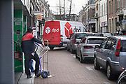 Nederland, Nijmegen, 10-3-2017Een medewerker van pakketbedrijf DPD levert bestellingen af in een winkelstraat. Hij heeft het busje gedeeltelijk op straat geparkeerd waardoor een onveilige verkeerssituatie is ontstaan. de chauffeur is een man met een Turkse achtergrond, Foto: Flip Franssen