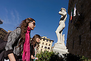 """Two female tourists walk beneath the perfect nude male example of Michelangelo's David statue in Piazza della Signoria. It is said that the statue's genitals were created smaller to imply that David was not allowing himself to make decisions with pleasure in mind. """"David"""" is a masterpiece of Renaissance sculpture created between 1501 and 1504, by the Italian artist Michelangelo. It is a 5.17 metre (17 feet) marble statue of a standing male nude. The statue represents the Biblical hero David, a favoured subject in the art of Florence but soon came to symbolise the defence of civil liberties in the Florentine Republic, an independent city-state threatened on all sides by more powerful rival states and by the Medici family."""