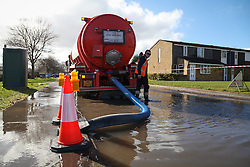 © Licensed to London News Pictures. 22/02/2014. Basingstoke, Hampshire. A tanker collecting water from a man hole on Grampian Way in the Buckskin area of Basingstoke, Hampshire. Groundwater levels are continuing to rise in the area, forcing 69 homes to be evacuated in the Buckskin Area of the commuter town. Photo credit : Rob Arnold/LNP