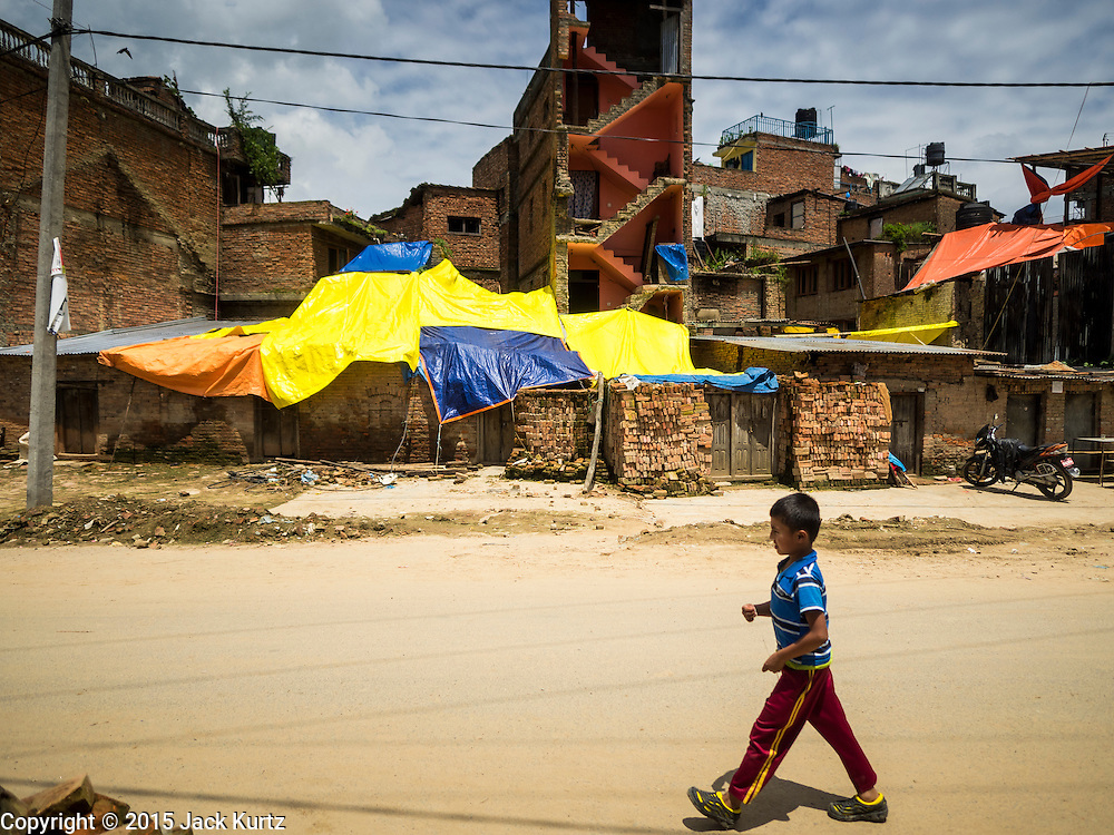 04 AUGUST 2015 - BUNGAMATI, NEPAL: A boy walks past buildings covered in tarps that were damaged in the earthquake in Bungamati, a village about an hour from Kathmandu. Three months after the earthquake many families still live in tents and temporary shelters scattered around the village. The Nepal Earthquake on April 25, 2015, (also known as the Gorkha earthquake) killed more than 9,000 people and injured more than 23,000. It had a magnitude of 7.8. The epicenter was east of the district of Lamjung, and its hypocenter was at a depth of approximately 15km (9.3mi). It was the worst natural disaster to strike Nepal since the 1934 Nepal–Bihar earthquake. The earthquake triggered an avalanche on Mount Everest, killing at least 19. The earthquake also set off an avalanche in the Langtang valley, where 250 people were reported missing. Hundreds of thousands of people were made homeless with entire villages flattened across many districts of the country. Centuries-old buildings were destroyed at UNESCO World Heritage sites in the Kathmandu Valley, including some at the Kathmandu Durbar Square, the Patan Durbar Squar, the Bhaktapur Durbar Square, the Changu Narayan Temple and the Swayambhunath Stupa. Geophysicists and other experts had warned for decades that Nepal was vulnerable to a deadly earthquake, particularly because of its geology, urbanization, and architecture.    PHOTO BY JACK KURTZ