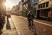 Een vrouw fietst in het avondlicht door Utrecht.<br /> <br /> A woman cycles in the evening in Utrecht.