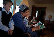 Mary Ethel Rhodes reads a story to Glenn and his younger brother Jesse before leaving for Sunday services. Sunday mornings are somber as families prepare for their church service. After the children are dressed in their Sunday best, they read or do quiet activities until they leave for church. Old Order Mennonites are a branch of the Mennonite church. It is a term that is often used to refer to those groups of Mennonites who practice a lifestyle without some elements of modern technology.
