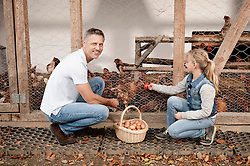 Father and daughter at henhouse on organic farm