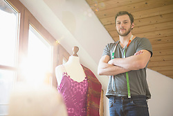Portrait of a male dressmaker standing with his arms crossed at dressmaker's model, Bavaria, Germany