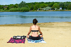 © Licensed to London News Pictures. 20/05/2020. LONDON, UK.  A woman sits on the beach as members of the public take advantage of the easing of certain coronavirus pandemic lockdown restrictions to enjoy the sunshine and warm weather at Ruislip Lido in north west London.   The forecast is for temperatures to rise to 29C, the hottest day of the year so far.  Photo credit: Stephen Chung/LNP
