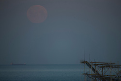© Licensed to London News Pictures.  27/04/2021. Brighton, UK. The supermoon also known as Pink Moon sets over Brighton Pier in East Sussex. A supermoon is a full moon or a new moon that nearly coincides with perigee--the closest that the Moon comes to the Earth. Photo credit: Marcin Nowak/LNP