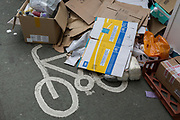A cycle lane is partially blocked by an overspill of rubbish and litter, covering the bike stencil, on 3rd August 2017, in London, England.