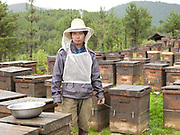Portrait of a beekeeper amongst his bee hives near Zongdian (Shangri-La). China currently produces half of the world's honey with the average beekeeping operation consisting of about 50 colonies. The Chinese economy is developing rapidly, and its beekeeping industry plays an important role in world trade.