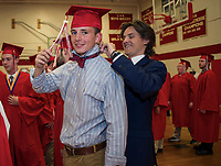 Tom Turpin helps classmate Riley Roy with his bow tie as the class of 2018 readies for their commmencement exercises at Laconia High School on Friday evening.  (Karen Bobotas/for the Laconia Daily Sun)