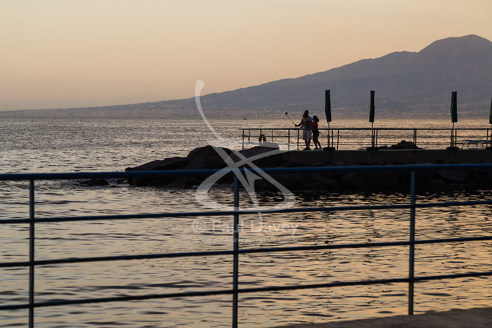 Sorrento, Italy, September 16 2017. A couple on the jetty at Marina Piccola take selfies at sunset, with Mt Vesuvius in the background in Sorrento, Italy. © Paul Davey