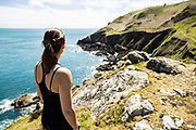 Woman out for a run on the North Coast cliff paths stopping and taking in the view of the sea and headland in Jersey, Channel Islands